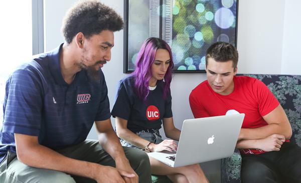Three students looking at laptop.